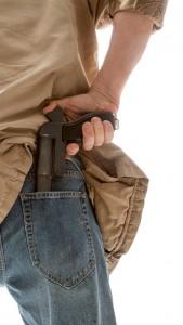 man holding gun behind back